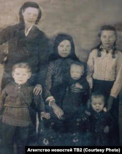 evdokiya sprava v beloj bluzke s mamoj i eshhe tremya rodivshimisya uzhe v ssylke bratyami i sestroj